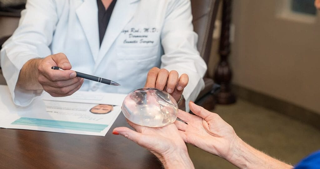 Breast Augmentation Consultation With Close Up of Silicone Implant Held By Patient and Doctor's Hands