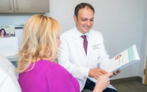 Dr. Rod Talking To Patient In Pink Blouse About Dermacare Services
